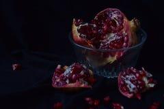 Stillife с гранатовым деревом и семенами в стеклянной вазе на черной предпосылке Стоковые Фотографии RF
