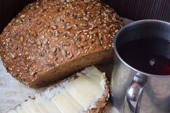 Stillife с некоторым хлебом, сандвичем с маслом и кружкой металла сладостного чая Стоковые Фото