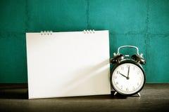 Stillife of desk calendar with alarm clock on wood table. Vintag Stock Photography