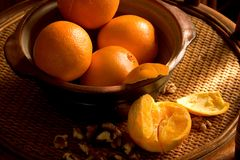 Stillife with oranges on rattan tray. Natural light image of stillife with oranges and walnuts Royalty Free Stock Photos
