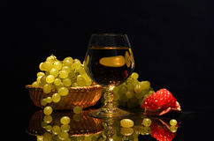 Stillleben auf einem dunklen Hintergrund Weinalkoholgläser, -granatäpfel und -trauben im Korb stockfoto