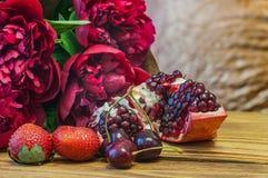Stillleben in den roten Tönen Pfingstrosen, Granatapfel, Kirsche und Erdbeere lizenzfreie stockfotos