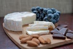 Stillleben der Brie, der Mandeln, der Schokolade und der Trauben Lizenzfreie Stockbilder
