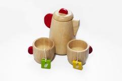 Stillleben der hölzernen Teekannen- und Schleppseilschalen, auf weißem Hintergrund Hölzerne Kinderspielwaren Stockfoto