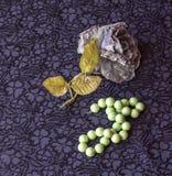 Stillleben der künstlichen Rose mit Malachitperlen auf Textilhintergrund stockbild