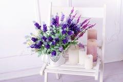Stillleben der Lavendelblume und -kerzen auf einem weißen Stuhl Stockfotos