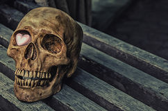 Stillleben der Schädel und das rosa Herz auf dem Holztisch Lizenzfreies Stockbild