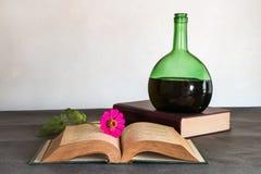 Stillleben des alten Buches und der Weinflasche Stockbild