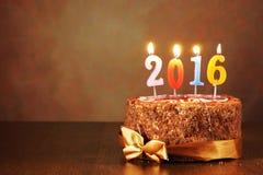 Stillleben 2016 des neuen Jahres Schokoladenkuchen und brennende Kerzen Lizenzfreies Stockfoto