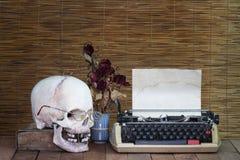Stillleben des Schädels mit alter Schreibmaschine, Buch mit trockenem stieg Stockfotografie