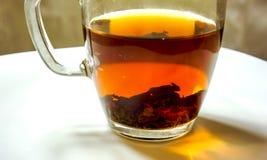 Stillleben des Tees in der Glasschale gegen Elfenbeintabelle Lizenzfreies Stockbild