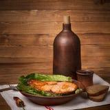 Stillleben in einer rustikalen Art backte Forelle und einen Krug Wein Stockbild