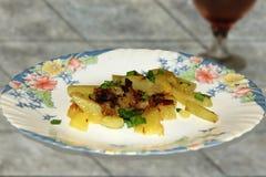 Stillleben: gebratene Kartoffeln und ein Glas Wein lizenzfreie stockfotografie