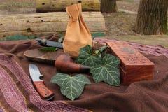 Stillleben gemacht von einem Rohr, ein Messer, eine Holzkiste und eine Schüssel und Efeublätter Stockbild