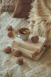 Stillleben im Hauptinnenraum des Wohnzimmers Strickjacken und Tasse Tee mit einem Kegel auf den Büchern gelesen Gemütliches Herbs lizenzfreie stockfotografie