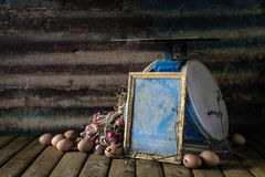 Stillleben mit altem Rahmen, Eiern, Zwiebeln und alten blauen Skalen Stockfotos