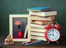 Stillleben mit Büchern, einem Wecker und einem Rahmen für ein Foto Stockbild