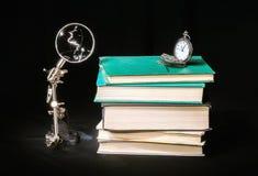Stillleben mit Büchern, Uhren und Lupe Lizenzfreies Stockbild
