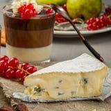 Stillleben mit Blauschimmelkäse, überlagertem Schokoladennachtisch im Glas, Moosbeere und Birne Lizenzfreie Stockfotos
