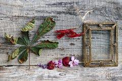 Stillleben mit Blumen, Blättern und einem Messingbilderrahmen Lizenzfreie Stockfotografie