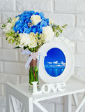 Stillleben mit Blumen, hölzernen Buchstaben und einem Weinlesefotorahmen Lizenzfreies Stockfoto