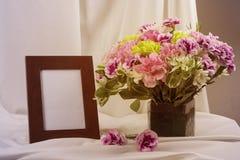 Stillleben mit Blumen und weißem Fotorahmen Stockfotos