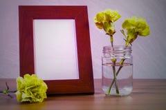 Stillleben mit Blumen und weißer Fotorahmen auf Holztisch ov Lizenzfreies Stockfoto