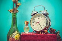 Stillleben mit defektem Wecker, alter Glasvase mit totem ROS Lizenzfreies Stockfoto
