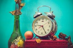 Stillleben mit defektem Wecker, alter Glasvase mit totem ROS Stockfotos