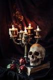 Stillleben mit dem Schädel, Buch und Kerzenständer Stockfotografie