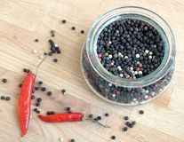 Stillleben mit den Samen des roten Paprikapaprikapfeffers und des schwarzen Pfeffers innerhalb des runden Glasgefäßes und auf höl Stockfotografie