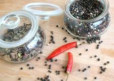 Stillleben mit den Samen des roten Paprikapaprikapfeffers und des schwarzen Pfeffers innerhalb des runden Glasgefäßes und auf höl Lizenzfreies Stockbild