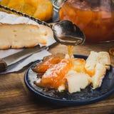 Stillleben mit den Stücken des Käses und des Confiture auf der blauen Platte Lizenzfreies Stockbild