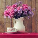 Stillleben mit einem Blumenstrauß von Herbstblumen und von Retro- eine Schale Lizenzfreie Stockfotos
