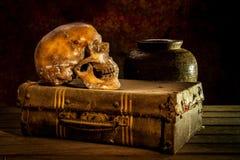 Stillleben mit einem menschlichen Schädel mit alter Schatztruhe und Gold, Stockfotografie