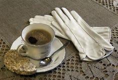 Stillleben mit einem Tasse Kaffee und Handschuhen Lizenzfreie Stockfotos