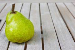 Stillleben mit einer großen grünen Birne auf einem weißen Holztisch lizenzfreies stockbild