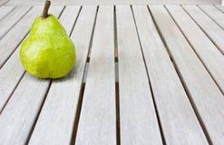 Stillleben mit einer großen grünen Birne auf einem weißen Holztisch lizenzfreie stockfotografie