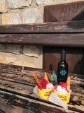 Stillleben mit einer Holzbank, einer Flasche Wein und Erdbeereis stockfotos