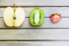 Stillleben mit einer Kiwi, einem Apfel und einer Erdbeere auf einem Holztisch lizenzfreies stockbild