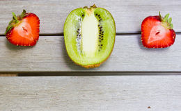 Stillleben mit einer Kiwi und einer Erdbeere auf einem weißen Holztisch stockfotografie