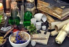Stillleben mit Flaschen, magischen Komponenten, Rollen und Büchern Lizenzfreies Stockfoto