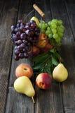 Stillleben mit frischen Früchten im Weidenkorb auf Holztisch Stockfotografie