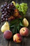 Stillleben mit frischen Früchten im Weidenkorb auf Holztisch Lizenzfreies Stockfoto