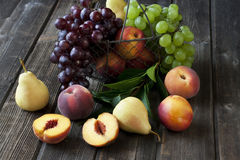 Stillleben mit frischen Früchten im Weidenkorb auf Holztisch Stockfoto