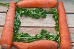 Stillleben mit 4 frischen Karotten und Petersilie auf einem hölzernen Hintergrund Lizenzfreies Stockfoto