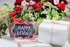 Stillleben mit frohe Feiertage Zeichen und Präsentkartons Stockfoto