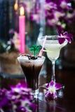Stillleben mit gefrorenem Kaffee mit Sahne, blüht Orchidee und brennt Stockfotografie
