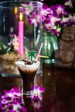 Stillleben mit gefrorener Orchidee des Kaffees mit Sahne blüht brennenden Ca Stockfoto