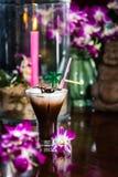 Stillleben mit gefrorener Orchidee des Kaffees mit Sahne blüht brennenden Ca Stockbilder